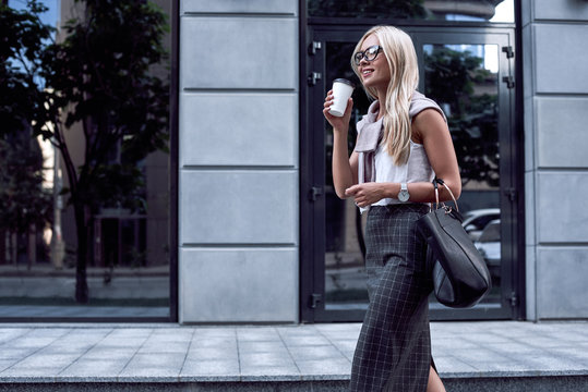 Young stylish woman walking on street of downtown with smile
