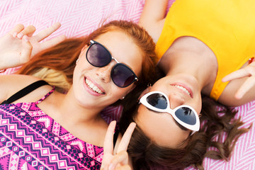 summer fashion, eyewear and people concept - smiling teenage girls in sunglasses lying on picnic blanket and showing peace hand sign