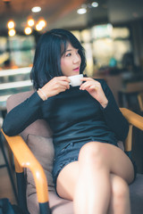 Beautiful attractive young Asian woman holding a cup of coffee or coffe in hand and sitting on sofa at cafe in the morning, vintage color tone.