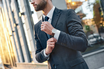 Cropped profile portrait of a successful young bearded guy in suit and glasses. So stylish and nerdy. Outdoors on a sunny street, fixing his cuffs