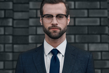 A confident view of the leader. A young businessman in glasses and with a beard looks directly at you