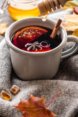 Mulled wine in grey rustic mugs with spices and citrus fruit on autumn background. Copy space.