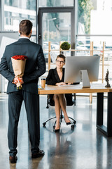 back view of businessman hiding bouquet of roses behind back to surprise businesswoman in office