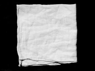 Crumpled white fabric cloth on black background