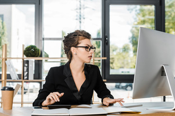 attractive businesswoman working and using computer in office