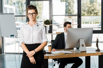 attractive businesswoman in shirt and skirt looking at camera in office