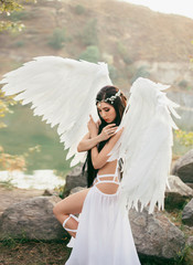 A heavenly angel in a fabulous, sexy dress with white wings, walks against the backdrop of cliffs and river, flooded with sunlight. Gorgeous, incredibly beautiful girl with long black hair. Art photo