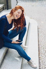 Young red-haired woman sitting on steps with phone