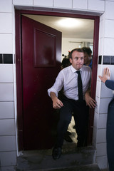 French President Emmanuel Macron makes his way through a doorway as he meets residents in the Quartier Orleans during a visit to the French Caribbean island of Saint-Martin
