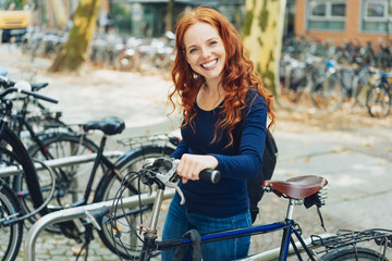 Pretty young redhead student parking her bike