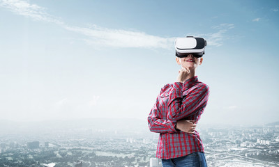 Girl in checked shirt wearing VR glasses experiencing another re