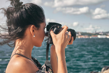 Wall Mural - Woman photographer, taking pictures of landscape at sea