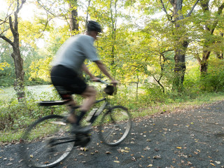Motion Blur shot of a tall adult male riding a rails to trails bike on a path in Connecticut