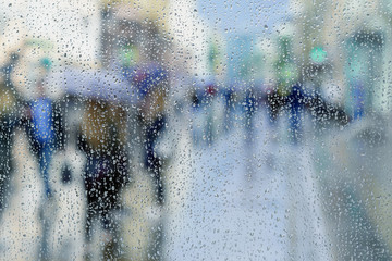 Rain drops on wet window, blurred people, city light bokeh. Concept of rainy weather, seasons, modern city. Copy space, for abstract background