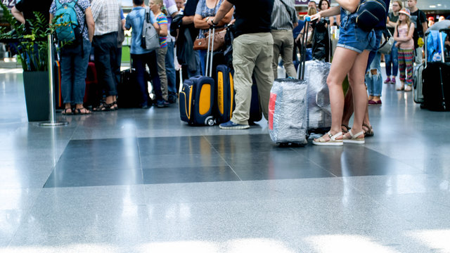 Photo of passengers feet and suitcases on floor at international airport terminal