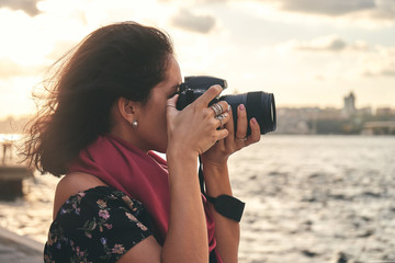 Wall Mural - Woman photographer with red scarf, taking pictures of landscape near sea at sunset