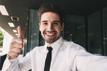 Business man near business center looking camera take a selfie.
