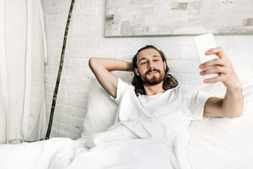 smiling Jesus taking selfie in bed during morning time at home