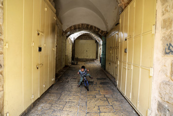 A boy rides his bicycle past closed shops during a general strike in support of an Israeli-Arab protest against Israel's Nation State Law,in Jerusalem's Old City