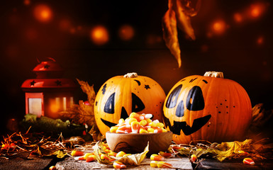 Halloween festive composition with sweet corn in bowl and smiling pumpkins guards, lantern, straw and fallen leaves on dark wooden background, rustic style, selective focus