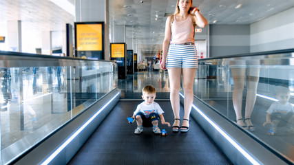 Young mother with toddler son standing on moving walkway at big modern airport