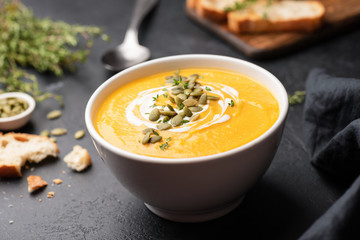 Pumpkin cream soup in bowl on black concrete background. Closeup view, selective focus. Autumn comfort food concept