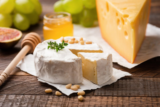 Cheese plate with brie, camembert, maasdam cheese and fruits green grapes, figs, pine nuts and thyme. Closeup view. Gourmet appetizer plate