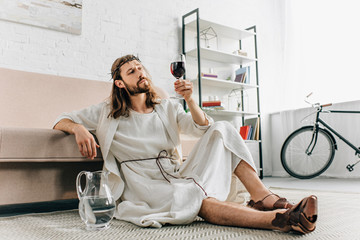 skeptical Jesus in crowns of thorns and robe sitting on floor near jug of water and drinking wine from glass at home