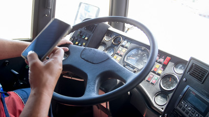 Closeup image of truck driver using smartphone while driving. Danger in transport. Irresponsible driver