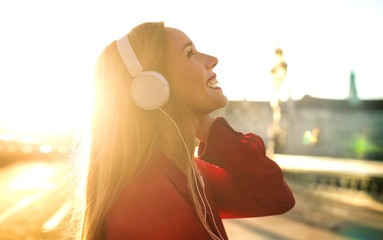 Beautiful girl listening music with headphones while walking in the street