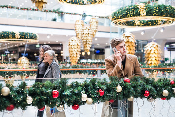 A portrait of teenage boy with smartphone in shopping center at Christmas.