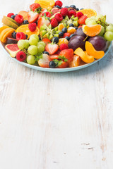Wall Mural - Healthy fruit platter, strawberries raspberries oranges plums apples kiwis grapes blueberries on the white wooden table, vertical, copy space for text, vertical selective focus
