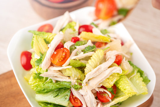Fresh and delicious homemade chicken salad with tomatoes and pomelos in wooden background, concept of healthy and diet, top view, copy space