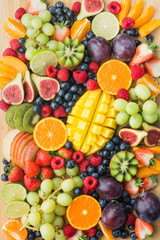 Assortment of healthy raw fruits and berries platter background, strawberries raspberries oranges plums apples kiwis grapes blueberries, mango, top view, vertical, selective focus