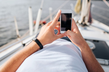 Picture of phone in man's hands. He holds in confident. Screen is dark. Phone is white. Young man lies on yacht board.