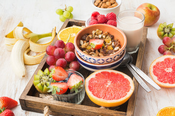 Healthy eating, paleo gluten free nut and fruit granola served with fruits and berries, nut milk, selective focus