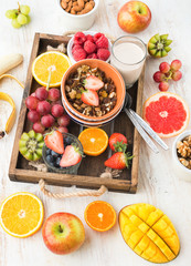 Paleo grain free nut and fruit granola served with fruits and berries, nut milk, vertical, top view, selective focus