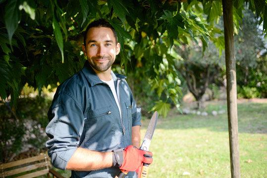 handsome young man gardener trimming hedgerow in a garden park outdoor