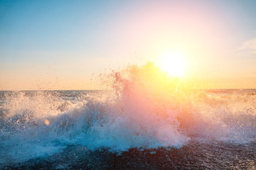 The sun shines through the spray of a sea wave from the shore