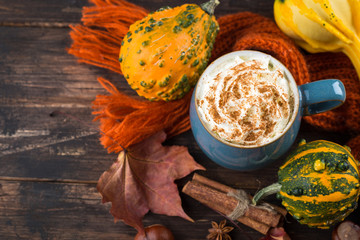 Pumpkin latte with spices and whipped cream on top on a wooden background. Copy space. Autumn or winter hot drink.