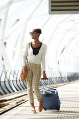 Full body happy travel woman walking with suitcase at train station
