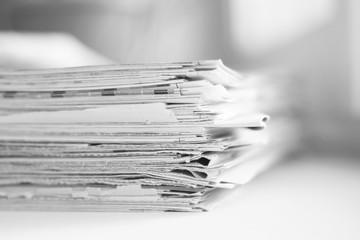 Lots of newspapers, magazines and journals pages folded and stacked in pile, selective focus on paper with blurred background. Could be used for news, information and communication concept