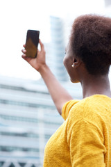 young african american woman taking selfie in the city
