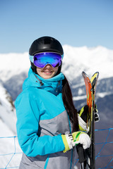Image of young smiling female athlete in helmet with skis in hand against blue sky