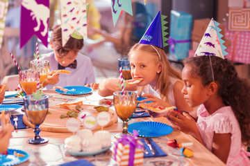 Kids eating pizza. Calm thoughtful children attending birthday party and eating pizza at the big table