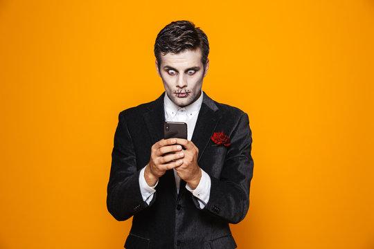 Shocked zombie man groom using smartphone isolated