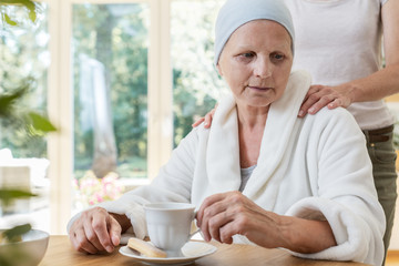 Family member supporting sick elderly woman with cancer while drinking tea