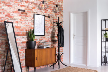 Mirror next to wooden cabinet in entrance hall interior with white door and poster on red brick...