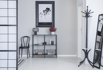 Poster above shelves with flowers and lamp in white simple hall interior with rack and black chair. Real photo