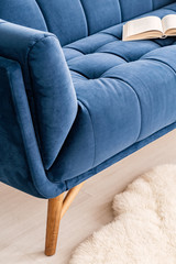 Close-up of a part a couch dressed in luxurious navy blue tapestry in a living room interior. An open book on the sofa. Real photo.